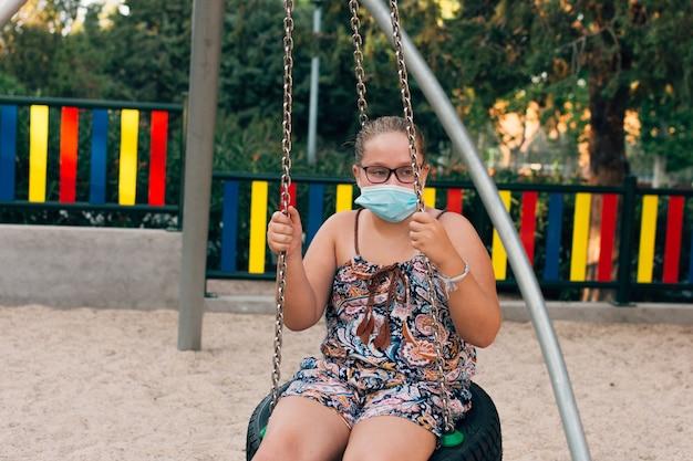 Fille blonde avec masque facial se balançant sur le parc