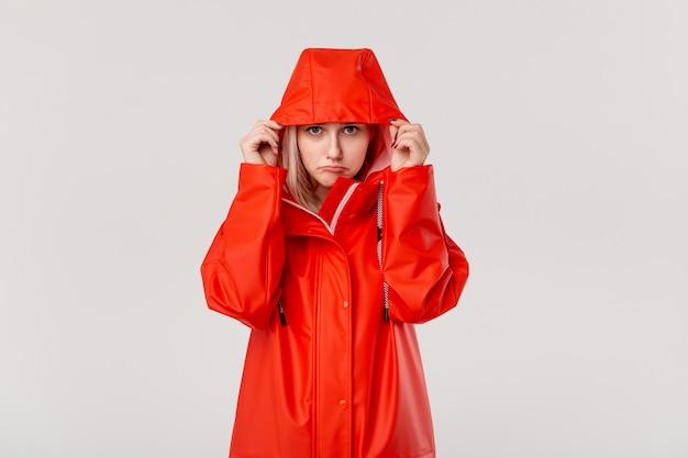 Fille blonde met le capuchon d'un imperméable rouge, commençant à pleuvoir.