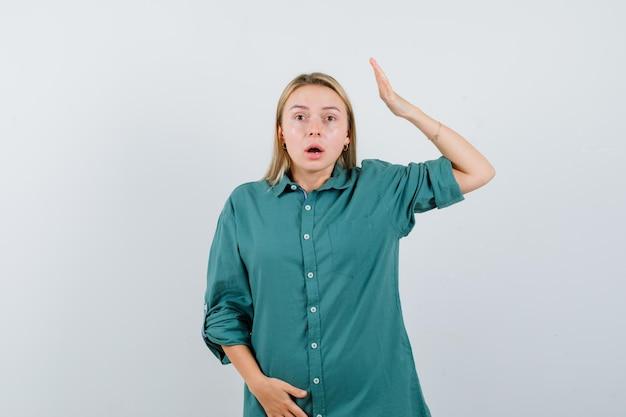 Fille blonde mettant la main au-dessus de la tête tout en tenant la main sur le ventre en blouse verte et à la surprise
