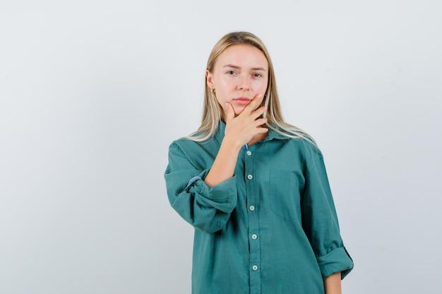 Fille blonde mettant la main sur le menton en chemisier vert et l'air sérieux.