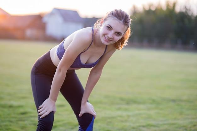 Fille blonde mince joue au sport et effectue des poses de yoga dans l'herbe d'été