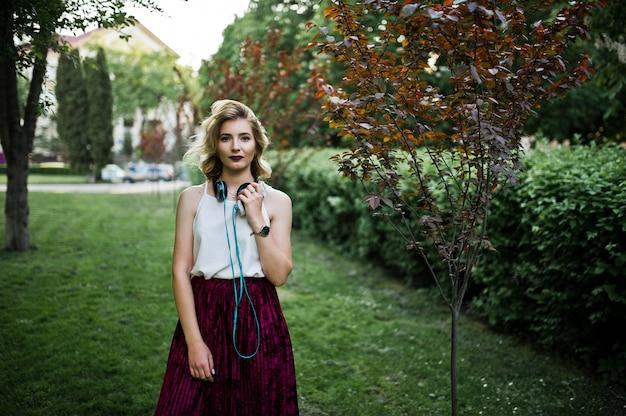 Fille blonde modèle à la mode et belle en élégante jupe en velours rouge velours, blouse blanche, a posé au parc avec téléphone et écouteurs.