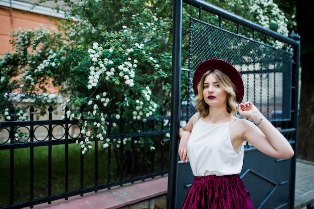 Fille blonde modèle à la mode et belle en élégante jupe de velours rouge en velours, chemisier blanc et chapeau, posant en plein air contre les portes.