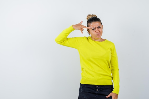 Fille blonde montrant le geste du pistolet près de la tête, grimaçant dans un pull jaune et un pantalon noir et l'air ennuyé