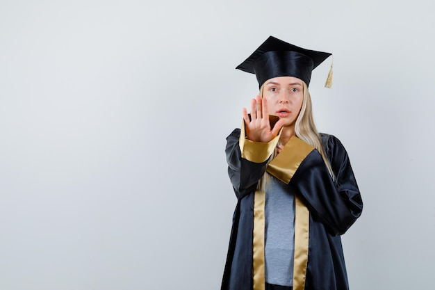 Fille blonde montrant un panneau d'arrêt, reposant la main sur la poitrine en robe de graduation et casquette et semblant sérieuse.
