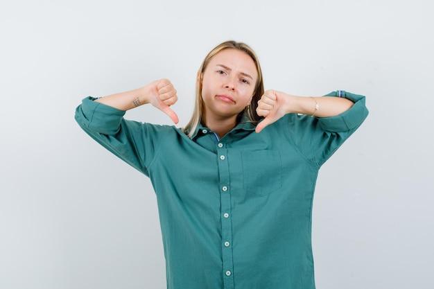Fille blonde montrant les pouces vers le bas avec les deux mains en blouse verte et l'air mécontent.
