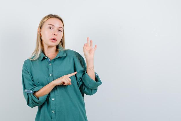 Fille blonde montrant un signe ok tout en le pointant en blouse verte et l'air sérieux