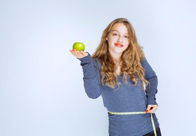 Fille blonde montrant son tour de taille tout en tenant une pomme verte.