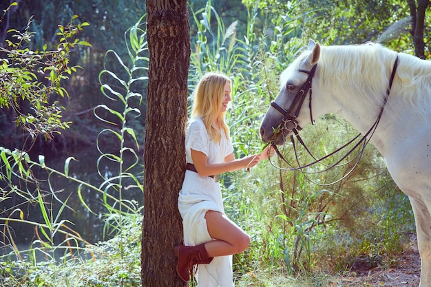 Fille blonde nourrir l'herbe à son cheval