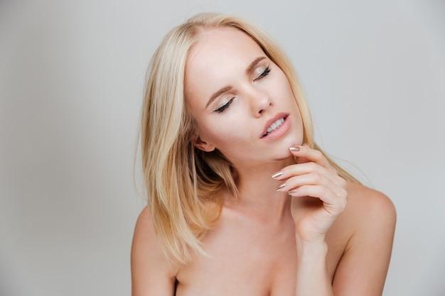 Fille blonde nue sensuelle aux yeux fermés posant isolé