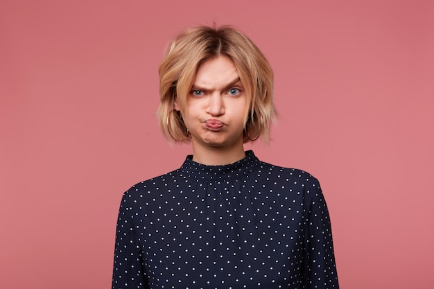Fille blonde offensée en colère bouleversée, fait la moue ses joues est submergée d'émotions négatives, de mauvaise humeur habillée en chemisier à pois, isolé sur rose