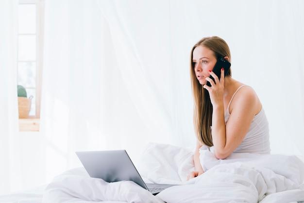 Fille blonde avec un ordinateur portable sur le lit