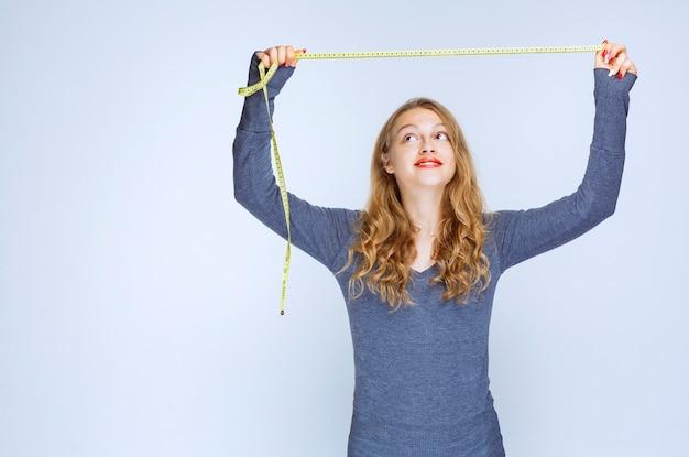 Fille blonde ouvrant le ruban à mesurer et montrant le résultat.
