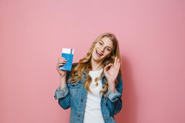 Une fille blonde avec un passeport avec billets de voyage et souriant sur fond rose