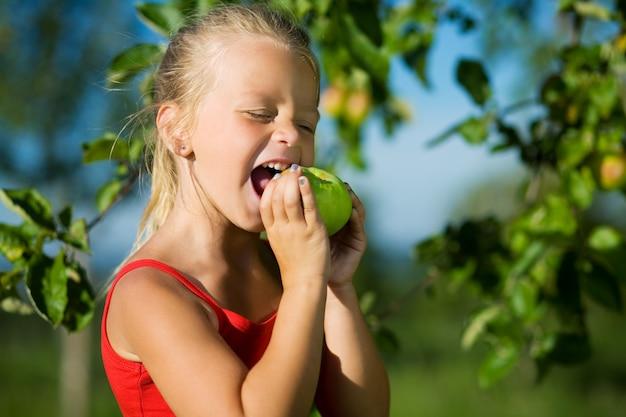 Fille blonde pique une pomme
