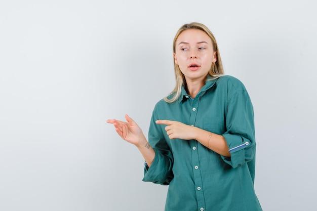 Fille blonde pointant vers la gauche avec l'index en blouse verte et à la radieuse