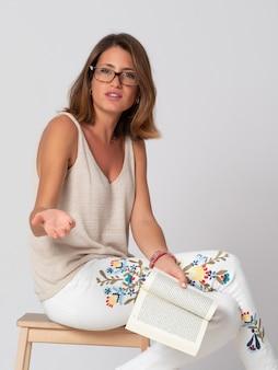 Fille blonde, portant des lunettes et vêtue de jeans blancs et de pulls beiges, lit un livre avec un fond blanc.
