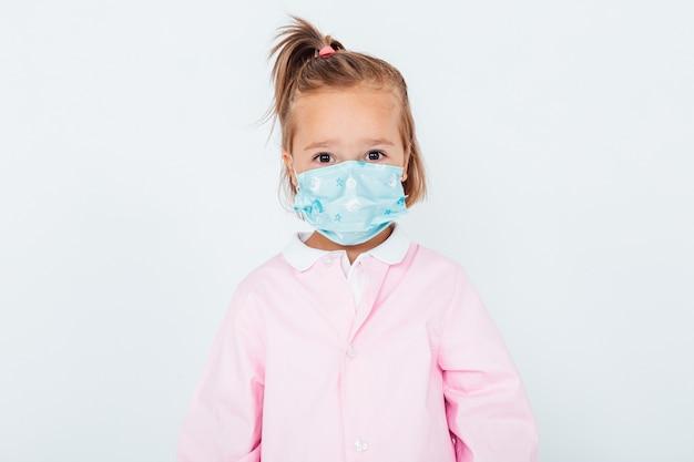 Fille blonde portant un tablier rose pour enfants et un masque chirurgical pour se protéger du covid-19