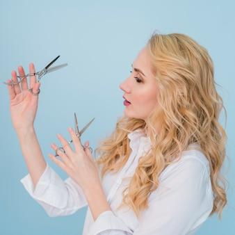 Fille blonde posant avec des ciseaux