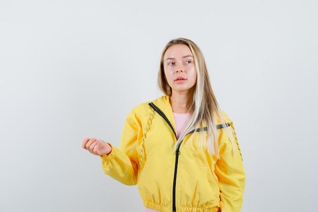 Fille blonde posant tout en regardant de côté en veste jaune et l'air curieux