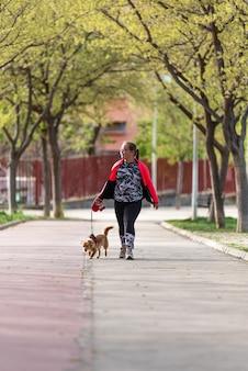 Fille blonde potelée avec des lunettes promenant son chien dans le parc.
