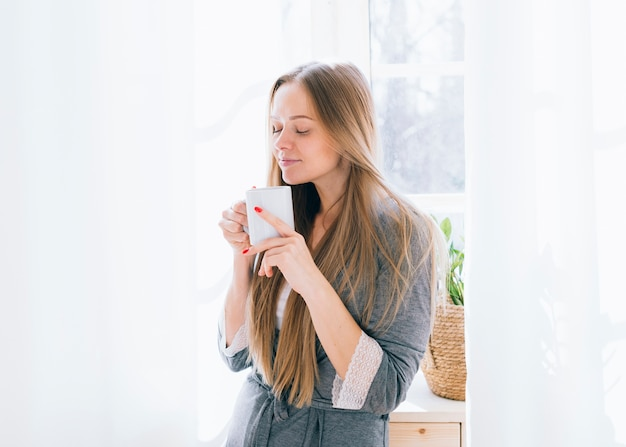 Fille blonde prenant un café le matin