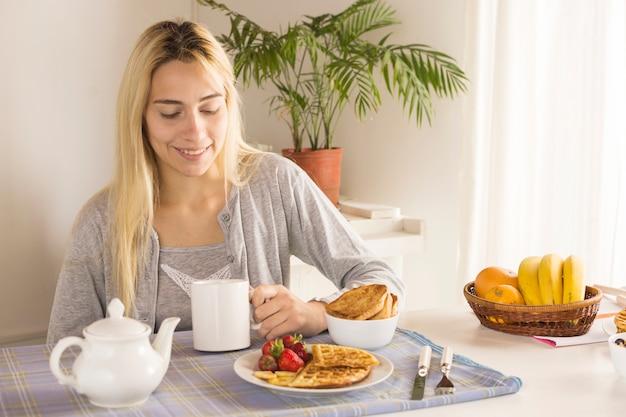 Fille blonde prenant son petit déjeuner