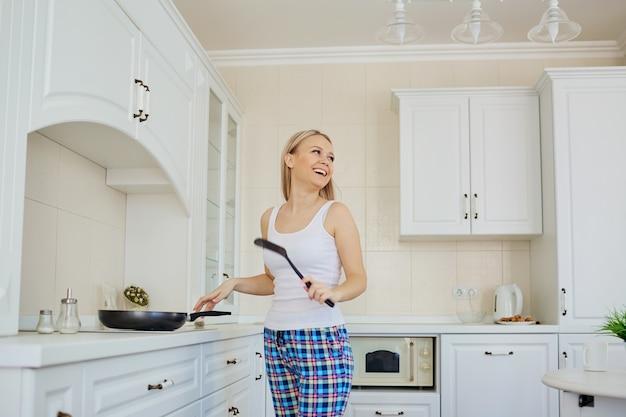 Une fille blonde en pyjama prépare le petit déjeuner dans la cuisine.
