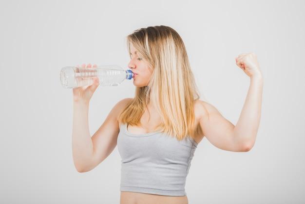 Fille blonde qui boit de l'eau