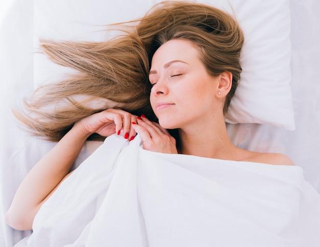 Fille blonde qui dort sur le lit