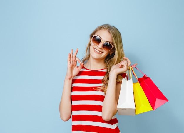 Une fille blonde qui est heureuse des achats qu'elle a faits et montre un geste sur fond bleu