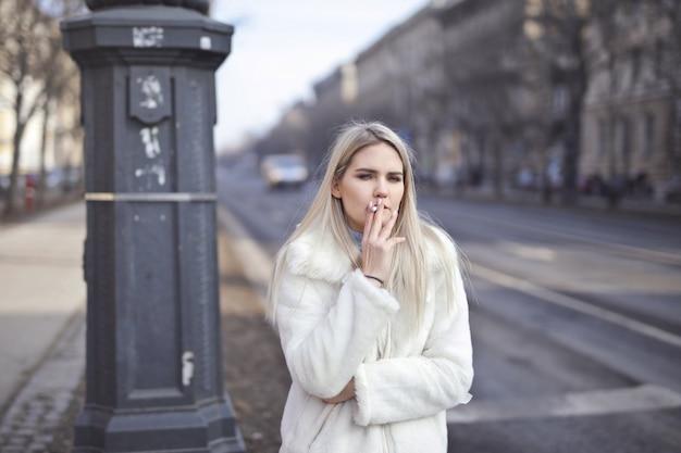Fille blonde qui fume en hiver