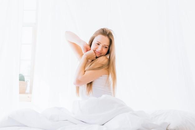 Fille blonde qui s'étend sur le lit