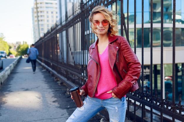 Fille blonde rêveuse marchant dans les rues, buvant du café ou un cappuccino. tenue d'automne élégante, veste en cuir et pull tricoté. lunettes de soleil roses.