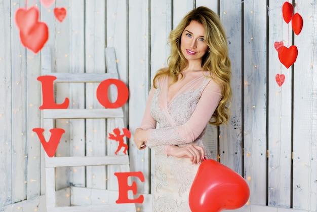 Fille blonde en robe blanche jouant avec des ballons rouges