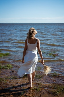 Une fille blonde en robe blanche marche pieds nus dans la mer tenant un bouquet de fleurs