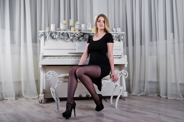 Fille blonde en robe noire posée près du piano avec décor de bougies de noël en salle blanche.