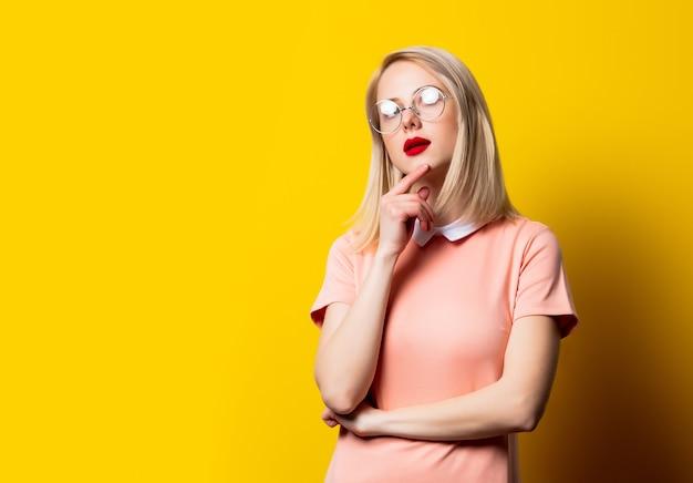 Fille blonde en robe rose et lunettes sur fond jaune