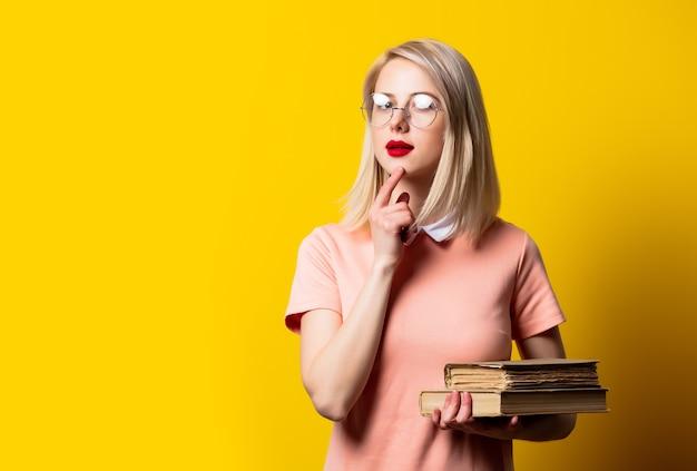 Fille blonde en robe rose et lunettes avec des livres sur fond jaune