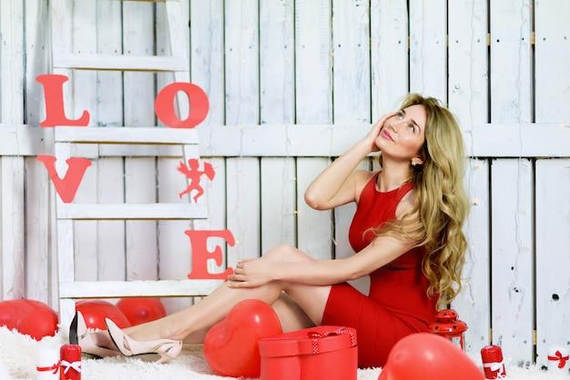 Fille blonde en robe rouge jouant avec des ballons rouges