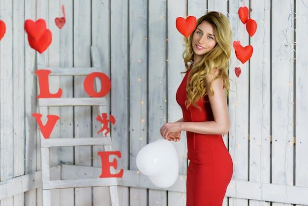 Fille blonde en robe rouge posant pour la saint-valentin avec des ballons