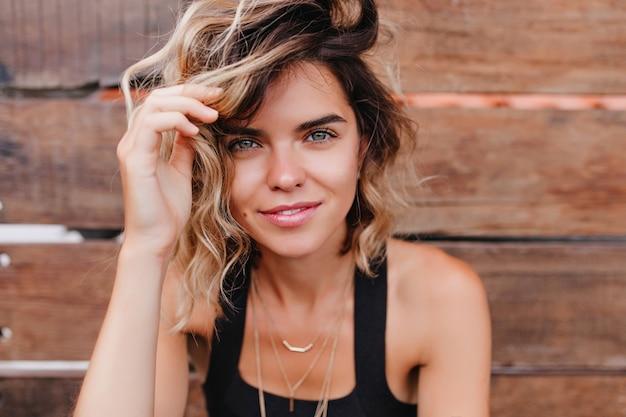 Fille blonde romantique se détendre pendant une séance photo en plein air. close-up portrait de jeune femme insouciante avec une peau bronzée isolée sur un mur en bois.