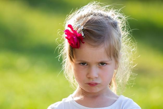 Fille blonde avec une rose rouge dans les cheveux semble en colère