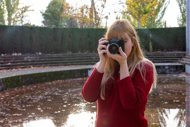 Fille blonde avec rouge à lèvres et pull en prenant une photo avec un appareil photo vintage