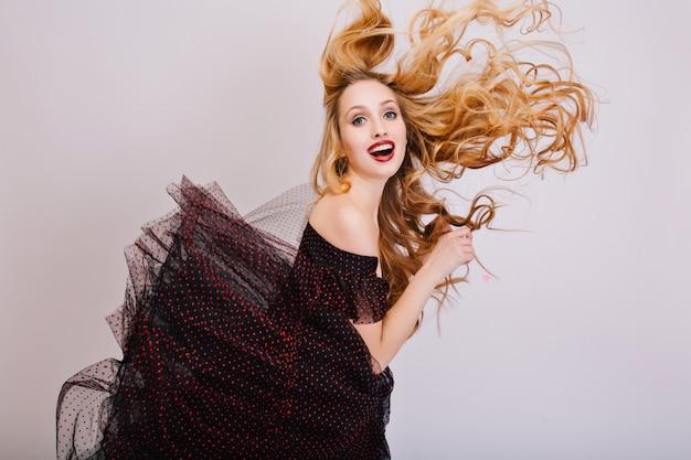 Fille blonde s'amusant, beaux longs cheveux bouclés en l'air, jeune femme posant. regard drôle avec la bouche ouverte. porter une robe noire avec une jupe moelleuse, un maquillage lumineux. isolé..