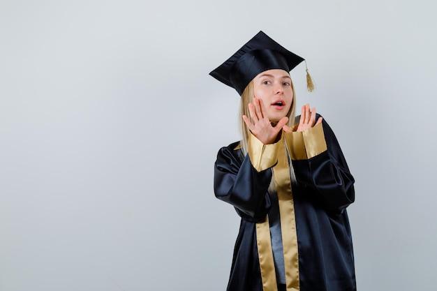 Fille blonde s'étendant les mains pour s'arrêter en robe de graduation et casquette et avoir peur