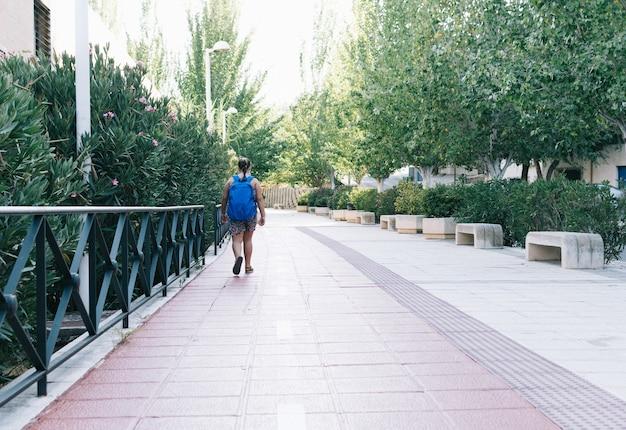 Fille blonde avec sac à dos bleu sur le chemin de l'école