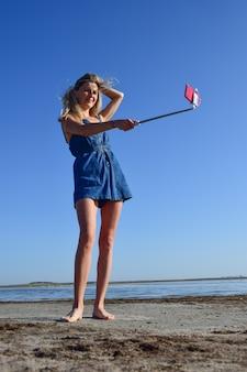 Une fille blonde en salopette en jean se tient au bord de la mer et prend un selfie