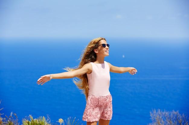 Fille blonde secouant les cheveux en l'air au bleu méditerranée