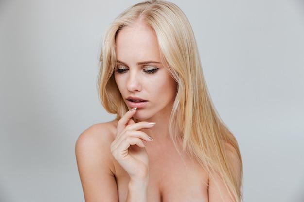 Fille blonde sérieuse avec les yeux fermés posant d'isolement